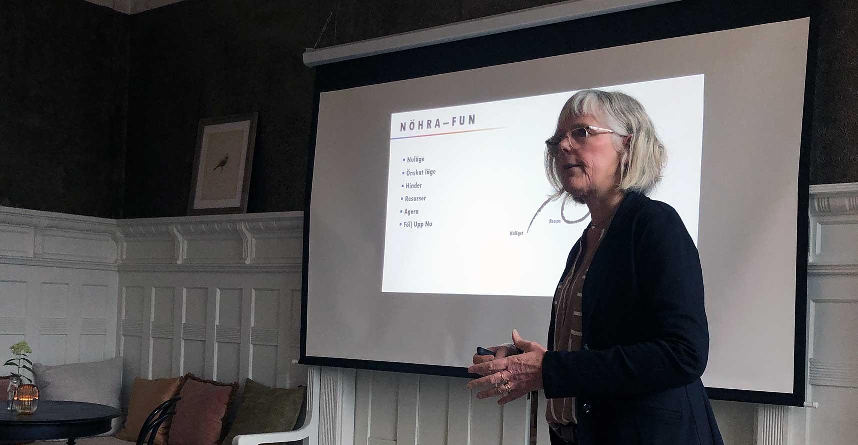 Ingegerd Bynert står framför en presentation som visar ett verktyg hon använder i sin ledarskapscoaching