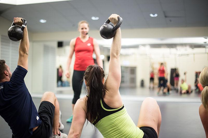 En träningsinstruktör i Friskis-kläder står framför två motionärer som håller i varsin kettlebell