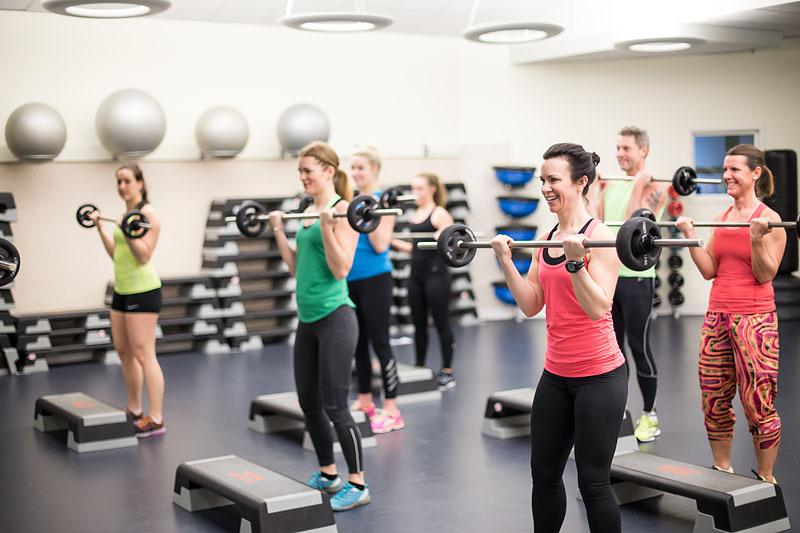 En grupp motionärer står och tränar med skivstänger i en träningslokal